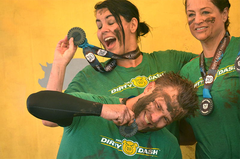 Racers showing off their Dirty Dash Race Medal